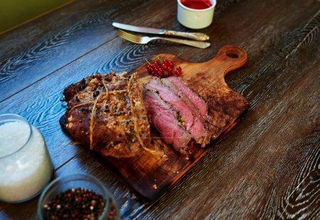 Photo pour Filet de veau savoureux cuit dans le four jusqu'au bleu rare, le cuisinier a servi sur une planche à découper, debout à côté de la sauce à la viande de baies sauvages - image libre de droit