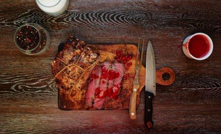 Photo pour Un grand morceau de filet d'agneau, cuit au four jusqu'à cuisson saignante, cook posé sur une planche de bois sur l'écorce et servira invités - image libre de droit