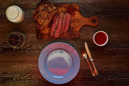 Photo pour Cuire cuire au four un grand morceau de porc bien assaisonné avec des épices et des herbes aromatiques, sur une table à côté une plaque sur laquelle poser prêt à cuire les biftecks, chiot - image libre de droit