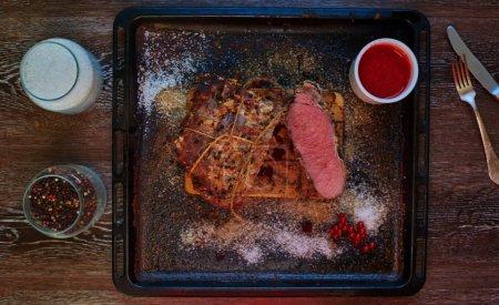Photo pour Vue de dessus sur la table est un plat qui est un gros morceau de viande de mouton, debout de sousostry prochain additionnée de raisins aigres - image libre de droit