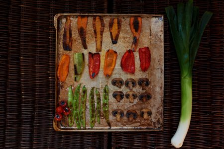 There are vegetables carefully arranged on a baking sheet