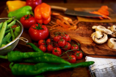 There are Fresh vegetables on a kitchen table