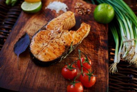 Foto de Filete grande de salmón al horno en el horno hasta oro marrón tumbado en una superficie de madera, para servir pescado tomate perfecto cebollino y limón, cocinero restaurante cocido piezas de salmón a la parrilla - Imagen libre de derechos