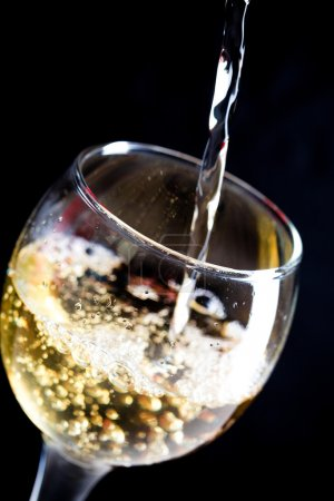 White wine pouring in wineglass