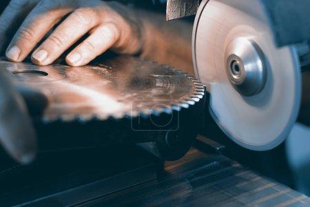Photo for Sharpening Circular Saw, worker sharpens a circular saw blade - Royalty Free Image