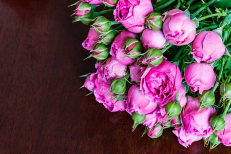 Bouquet of beautiful pink peonies, roses with green leaves lie on a wooden table