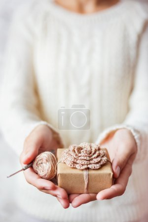 Woman in white knitted sweater holding a present and coil of thread with crochet hook. Gift is packed in craft paper with hand made crocheted flower. Example of DIY ways to pack Cristmas and other presents.