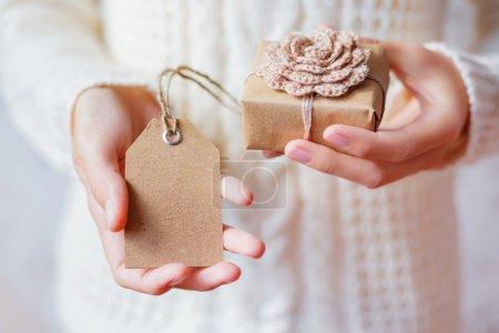 Photo pour Femme en pull tricoté blanc tenant un cadeau. Cadeau est emballé dans du papier artisanal avec fleur crochetée à la main. étiquette vide pour votre texte. Maquette-toi. Exemple de bricolage façons d'emballer Cristmas et autres cadeaux . - image libre de droit