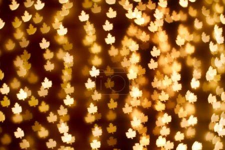 Blurring lights bokeh background of golden leaves