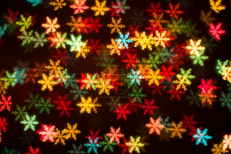 Blurring lights bokeh background of colorful snowflakes