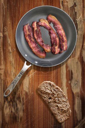 Fried Pork Bacon rashers in Teflon Frying Pan with slice of Bread on old Wooden Table