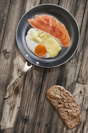 Prosciutto Rashers with Fried Egg and Edam Cheese in Teflon Frying Pan with Bread Slice on Old Cracked Wooden Table