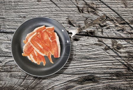 Prosciutto Rashers in Teflon Frying Pan on very Old Cracked Wooden Table
