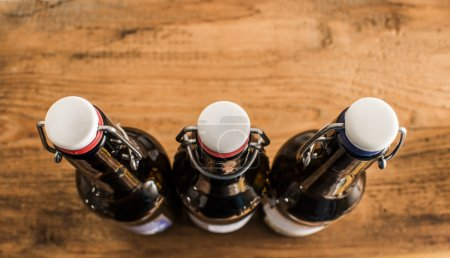Photo for Closed dark brown beer bottles with old-fashioned stopper stand on wooden texture table. empty copy space for inscription or object. - Royalty Free Image