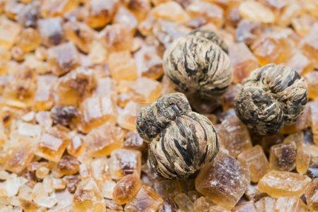 Photo pour Feuilles de thé sèches chinoises sur le symbole du cristal de sucre brun sur fond de bois. nourriture et boisson fond - image libre de droit