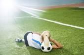 Young football girl lie on ball