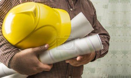 Photo pour Pas de visage Personne méconnaissable travailleur de la construction homme tenant dans les mains le modèle et le casque jaune sur le mur de texture verte avec fond de papier peint Espace de copie vide pour l'inscription - image libre de droit