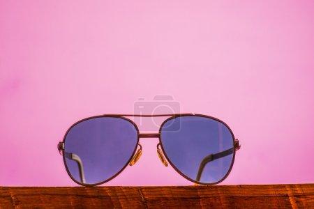 Photo pour Lunettes de soleil aviateur unisexe pourpre violet sur fond de mur rose - image libre de droit