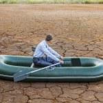 Business man stops in boat   on crack soil in  des...