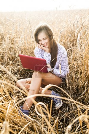 Photo for Portrait of Young latin  woman in shirt working on laptop in  summer wheat field - Royalty Free Image