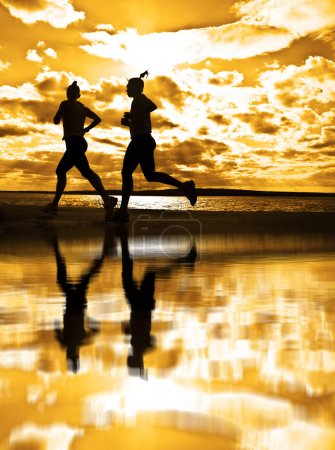 Silhouettes of two women running