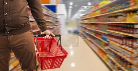 Photo pour Homme portefeuille commercial et tenant un panier en plastique sur le supermarché - image libre de droit