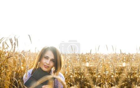 Photo pour Portrait de jeune femme latine adulte assis sur blé doré champ tenue livre avec visage souriant - image libre de droit