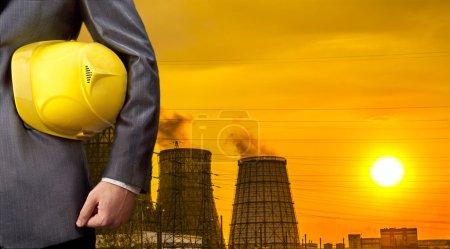 Foto de Mano o brazo del ingeniero sostienen casco de plástico amarillo para la seguridad de los trabajadores sobre Central Electric Heat CHP en invierno Espacio vacío para inscripción Cielo amarillo al atardecer con nubes - Imagen libre de derechos