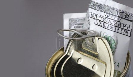 Dollar banknote in opened metal jar against gray b...