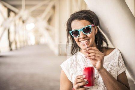 Photo pour Portrait extérieur de adolescente africaine boisson boissons fraîches fille. Mignon afro américaine femme porter moderne élégant lunettes de soleil vide perspective espace pour l'inscription - image libre de droit