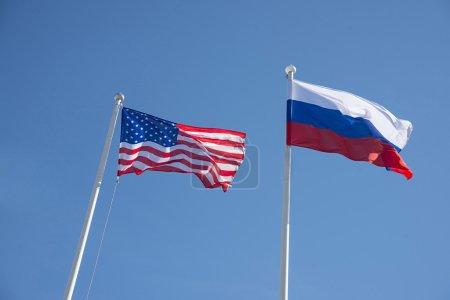 Photo pour Fédération de Russie et les États-Unis drapeaux sur un fond de ciel bleu. idée de la guerre de sanctions combattre la négociation et la confrontation - image libre de droit