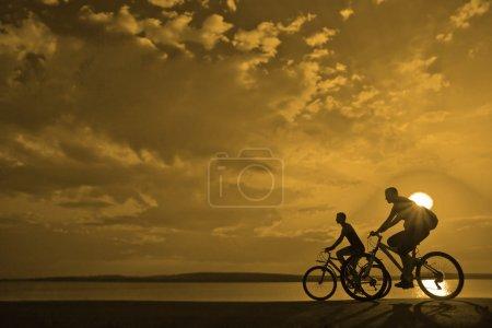 Photo pour Espace vide. Amis sportifs à vélo au coucher du soleil. Silhouettes de cyclistes sur la côte . - image libre de droit