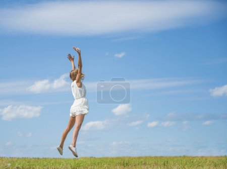 Woman Jumping  on a Grass Hill