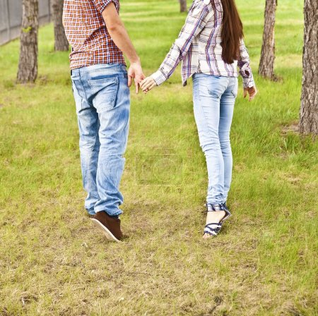Photo for Back view of young adult couple holding hands and walking in summer park on fresh green grass along trees in perspective. full length. Blue jeans and shirts. - Royalty Free Image