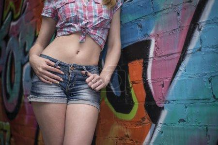 woman posing by  graffiti texture