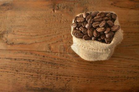 Photo pour Sac en toile de jute de café torréfié sur une table en bois vintage rétro, vue sur le dessus. espace de copie vide pour inscription ou objets - image libre de droit
