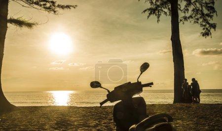Photo pour Jeunes gens marchant le long de la plage. Moto - image libre de droit