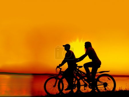 Couple of cyclists standing on  coast.
