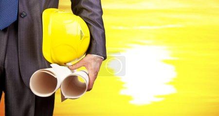 Photo pour Travailleur de la construction tenant des plans et un casque jaune - image libre de droit