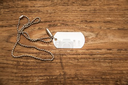 Photo for Metal Blank silver tag on a ball chain onold wooden desk. Empty copy space for inscription - Royalty Free Image