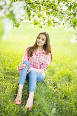 girl sitting down under tree