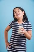 Indická dívka se sklenicí mléka, konzumního mléka Asiatka ve sklenici, portrét malé dívky, konzumní mléko ve sklenici