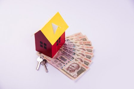 buying home on loan or rent concept using model house, calculator, indian currency notes, pen and spectacles