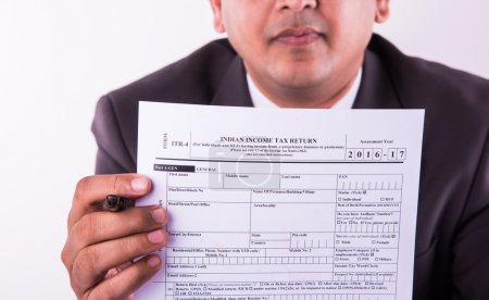 indian businessman showing indian income tax return form or ITR-4 form or form no. 16 of income tax department of india, selective focus