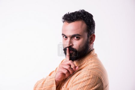Indian bearded man showing keep silence sign, Young indian man with beard keeping finger on lips asking for silence
