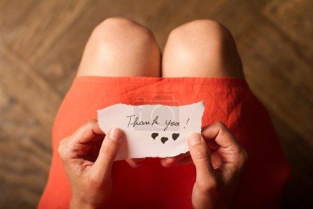 Photo pour Vue de dessus d'une femme avec une robe rose tenant une note de remerciement dans sa main - image libre de droit