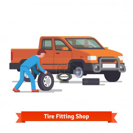 Car mechanic rolling tire to change it