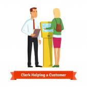 Clerk helping woman at information kiosk