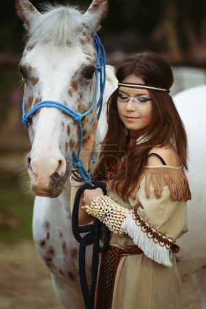 Young Indian girl walk with white horse portrait