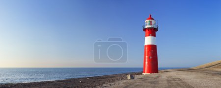 Красно-белый маяк и ясное голубое небо